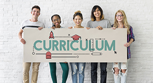 Students holding a sign saying curriculum